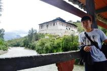 Scott at Archaic wooden cantilever Bridge with imposing Paro Dzong at Backdrop